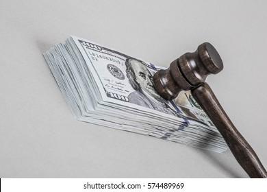 Wooden gavel on American Dollars on grey