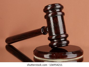 Wooden gavel on brown background