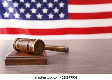 Wooden gavel on table against blurred USA flag