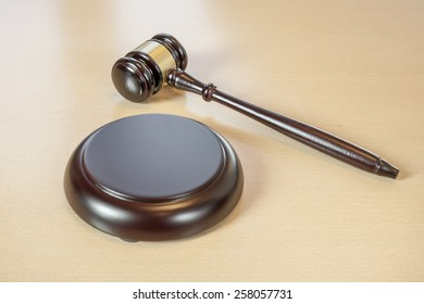 A wooden gavel on wooden table, on brown background