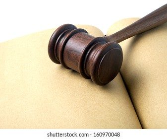 Wooden gavel and open notebook isolated on white background