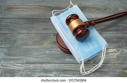 Wooden gavel Resting On A Protective Mask on a wooden table.