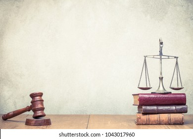 Wooden gavel, Vintage law scales and books on the desk front concrete wall background. Symbols of justice. Retro old style filtered photo