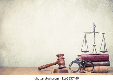 Wooden gavel, Vintage law scales, handcuffs and books on the desk front concrete wall background. Symbols of justice still life. Retro old style filtered photo