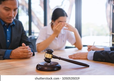 wooden gavel and wedding ring with lawyer working for deciding on marriage divorce clients in background. Family law concept.