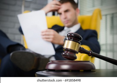Wooden gavel, working lawyer in background. attorney business judgment justice suite analyzing authority background concept