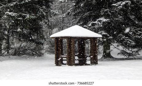 Wooden gazebo in snowy weather in central park, heavy snow, winter scene