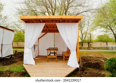wooden gazebo with white curtains for lunch in nature. construction and garden furniture for a country house