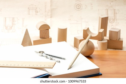 wooden geometric shapes and a notebook for recording