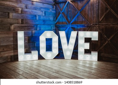 Wooden glowing love text letters. Rustic wedding dance floor lamp.
