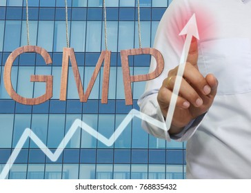 Wooden GMP text Stands for Good Manufacturing Practice hanging on rope and businessman point to the top of the graph on Skyscraper background.