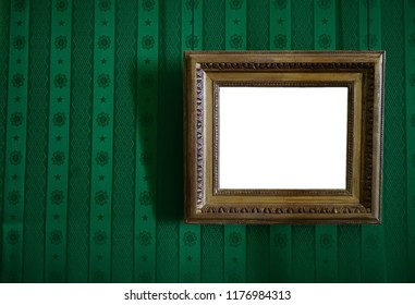 wooden and golden frame hang on green wall background. emty blank. vintage, retro wallpaper with pattern
