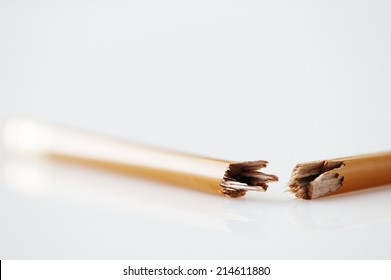 Wooden graphite pencil snapped in half lying on a white surface conceptual of anger, frustration and pressure in the office