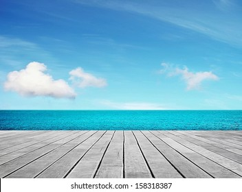 Wooden gray pier on sunny day with blue sky