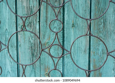 Wooden green background, stained with age and some paint peeling off with metal decor on top