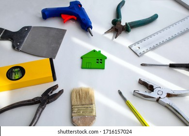 Wooden green house toy and construction tools on a white background. Real Estate Concept, Financial Credit Business Concept, Service Repair Concept. Flat lay.