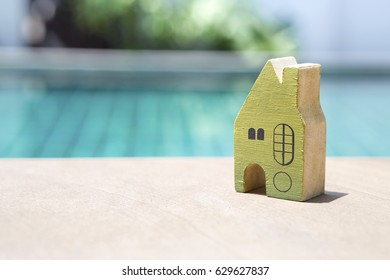 Wooden green miniature house over swimming pool background, real estate and home buyer concept