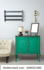 Wooden green vintage sideboard with empty wooden ornate brown desktop photo frame, flower planter, table lamp and cream tub chair on off white wall  including clipping path for the photo frame