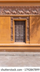 Wooden grid window installed in ornamental wall outside of old stone building