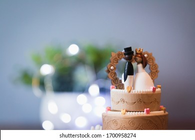 Wooden Groom kissing bride on wedding cake music box with fairy lights in the background and green plant. Wedding gift. Cake decoration and topper and a couple kissing. Gentleman with a top hat.