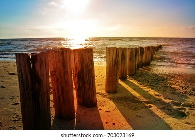 Wooden groynes at the North Sea beach at orange sunset