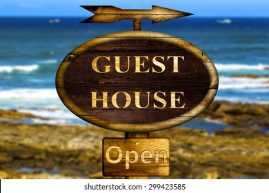 Wooden Guest house sign with a ocean background.