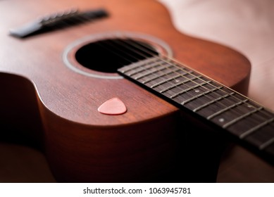 Wooden guitar with lighting on the body to show texture of guitar and pick