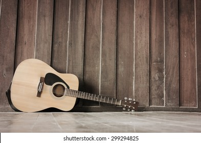 Wooden guitar lying against the wall