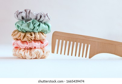 Wooden hairbrush and Lot of Colorful silk Scrunchies on white. Luxury Hairdressing tools and accessories. Hair Scrunchies, Elastic HairBands, Bobble Sports Scrunchie Hairband