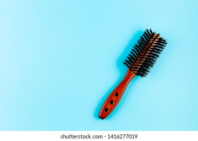 wooden hairbrush with natural boar bristles on blue background, Hair beauty salon equipment comb, copy space, top view, mockup
