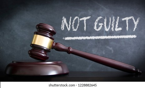 Wooden hammer in a courthouse at veredict of NOT GUILTY in a judgement. Hand written concept with chalk and empty copy space for Editor`s text.