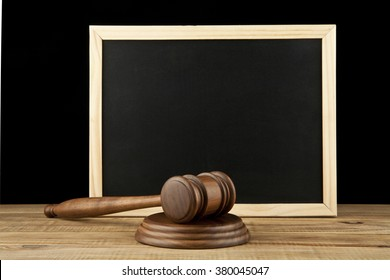 wooden hammer and a memo Board on black background