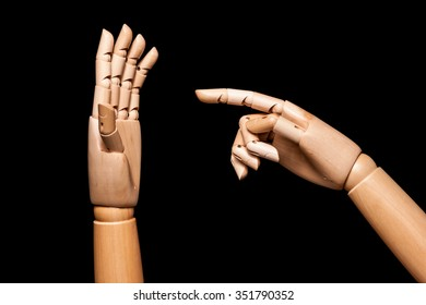A wooden hand accuses, the other is justified