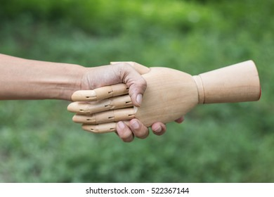Wooden hand and men hand in handshake to show friendship and respect on nature background. With copyspace.