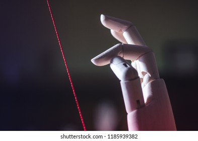 Wooden hand touching a delicate red string
