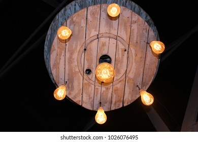 Wooden handcrafted light hanging from roof, silhouetted against a dark background