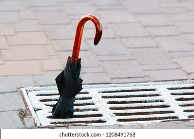 Wooden handle of an umbrella cane. Left  closed umbrella in manhole cover metal lattice for water drain on the road. Accessories for rainy day. Lost things on the street