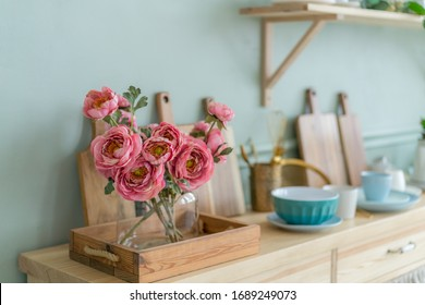 Wooden handmade kitchen surface. Many different tableware on the table. Flowers in the glass vase - Shutterstock ID 1689249073
