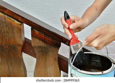 A wooden handrail is painted in brow color