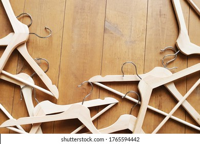 Wooden hangers are randomly scattered on the floor. Trying on clothes, changing clothes. Copy space. Flat lay.