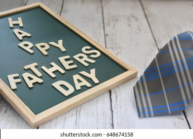 Wooden happy fathers day words on blackboard with necktie on wooden background
