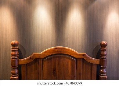 Wooden headboard in a dark bedroom lit by down lights on the ceiling