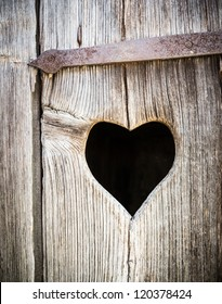 wooden heart at an antique restroom-door