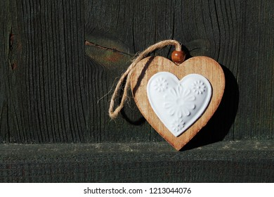 Wooden heart with ceramic in front of a dark green wooden wall, christmas decoration