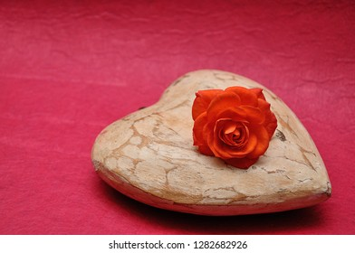 A wooden heart displayed with an orange rose