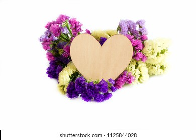 Wooden heart and flowers on white background