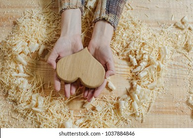 A wooden heart in the gentle hands of a girl on a wooden bench among the sawdust. Handmade on woodvintage carpentry tools. woodworking, craftsmanship and handwork concept, flat lay