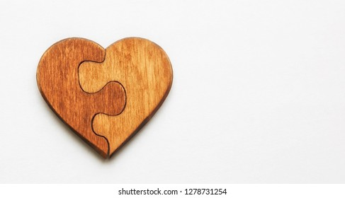 The wooden heart made like a puzzle isolated on white background. Valentines concept
