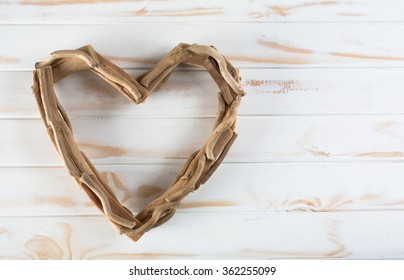 A wooden heart made out of sticks on a white wooden table