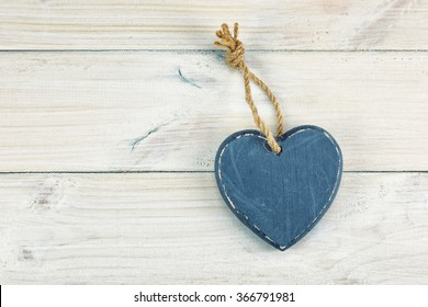 A wooden heart on a wooden background.